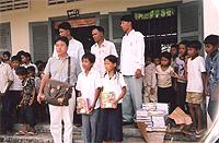 支援者の井狩氏と先生、子ども達。 おみやげの文具を持って。
